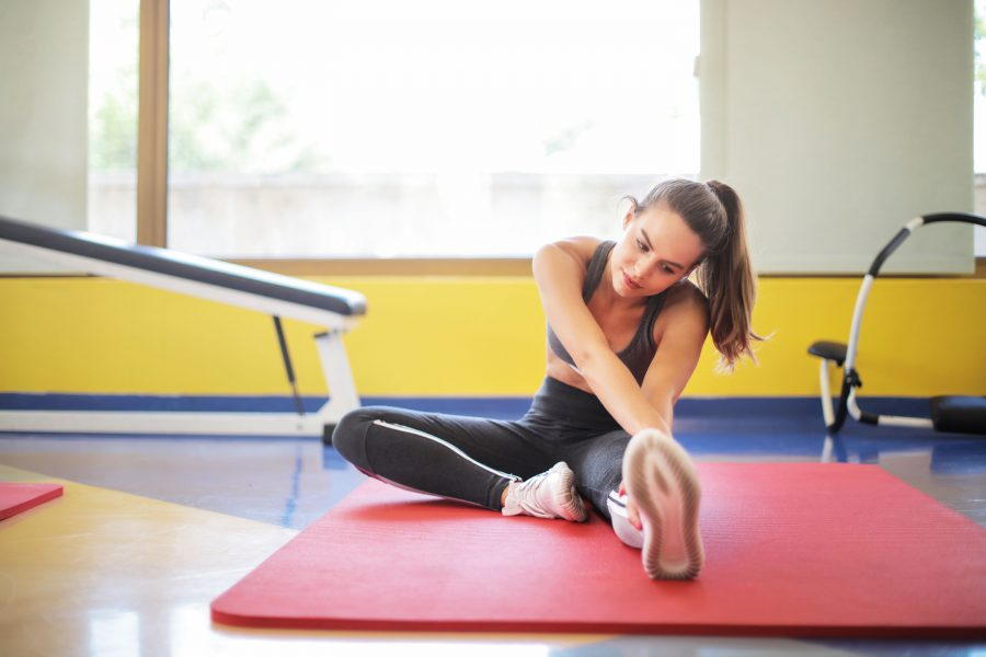 A woman stretches on an exercise mat.