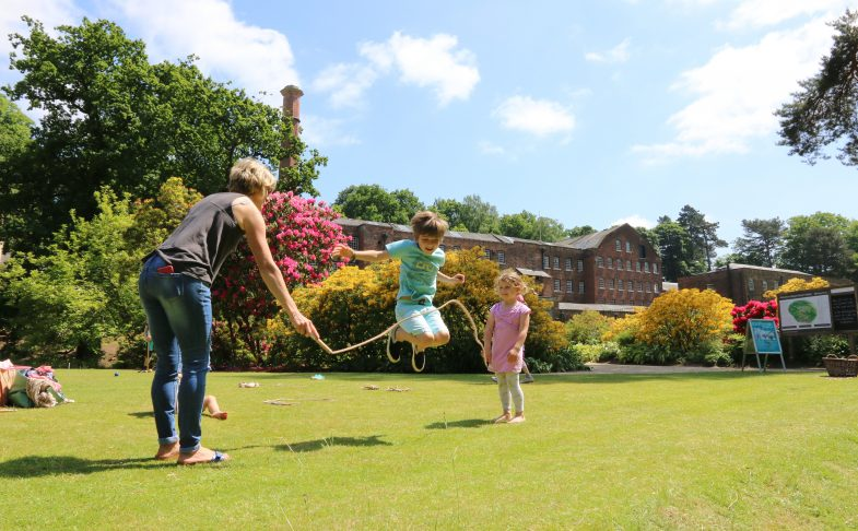 Two small children and their guardian have fun skipping in a large garden.