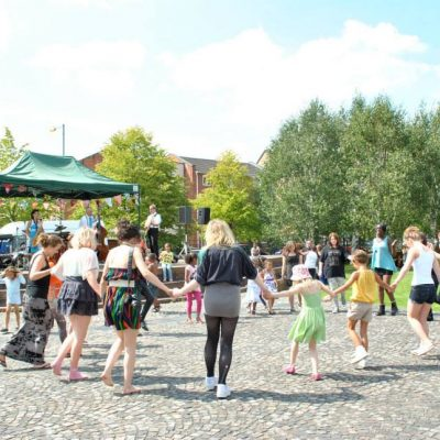 People dance in a circle in Hulme Park