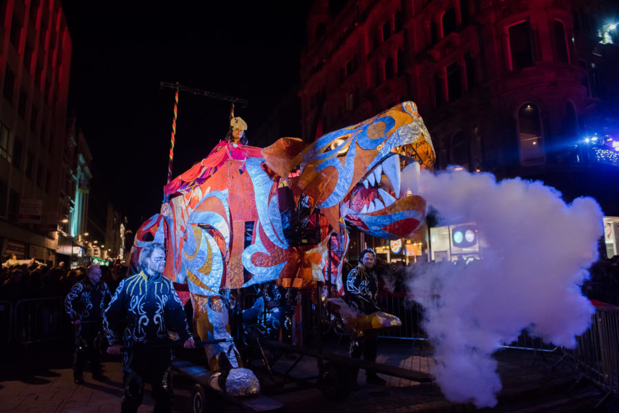 Large animal puppets in a street at night