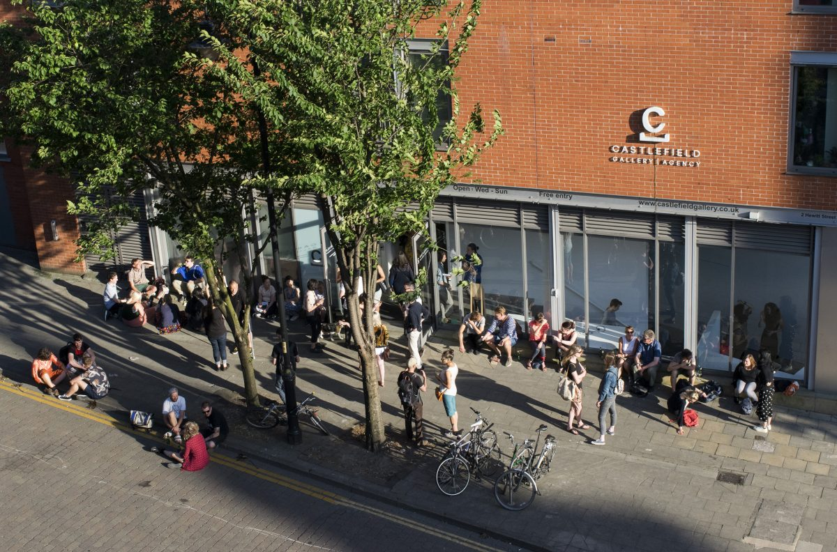 A group of people outside a gallery in the sun