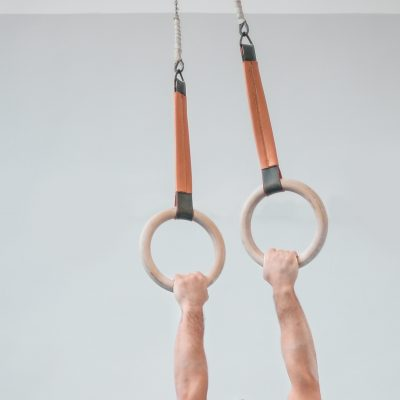 Closeup of a person's arms holding onto sports rings