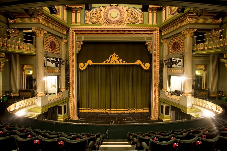 Empty theatre, with green curtains on the stage