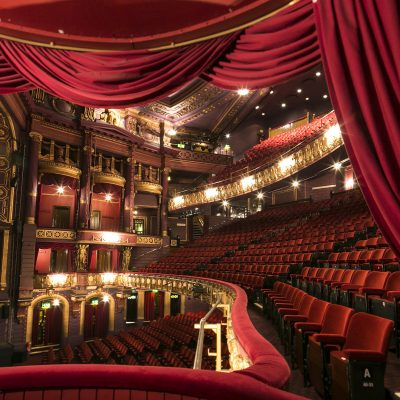 Empty theatre, with red velvet seats and curtains