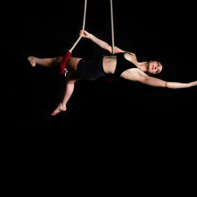 A woman hangs from ropes showing circus skills