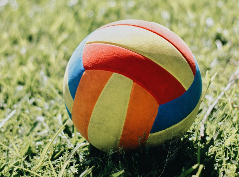 Closeup of a football on grass in the sun