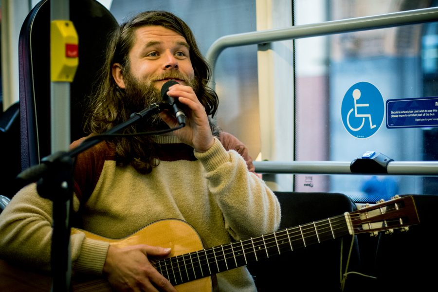 A guitarist plays music on a bus