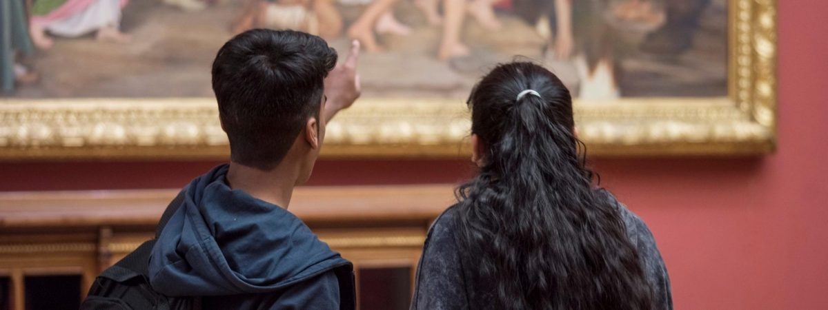 Woman and a man looking at a painting.