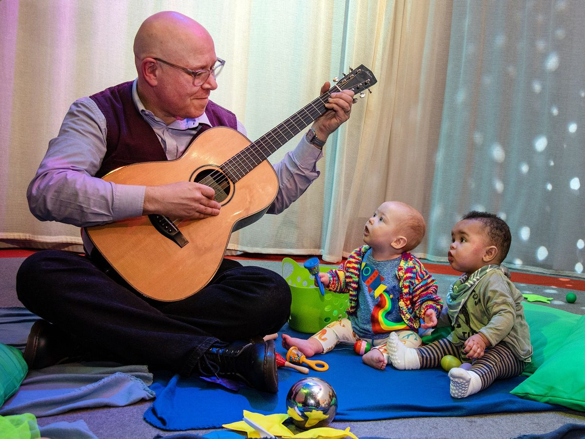A man plays a guitar and sings to two small children