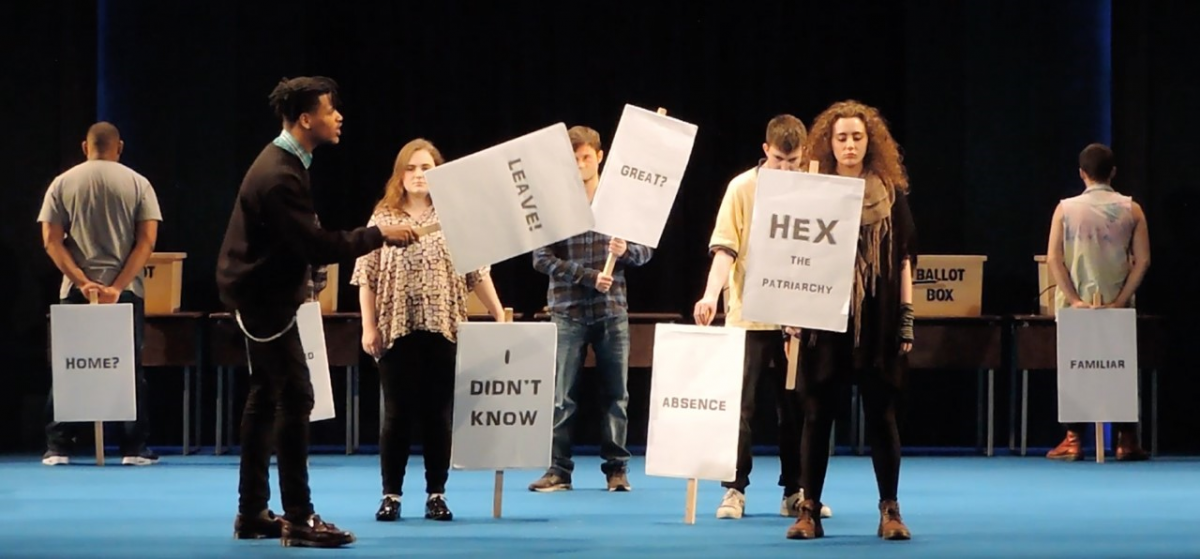 Young people on stage holding signs