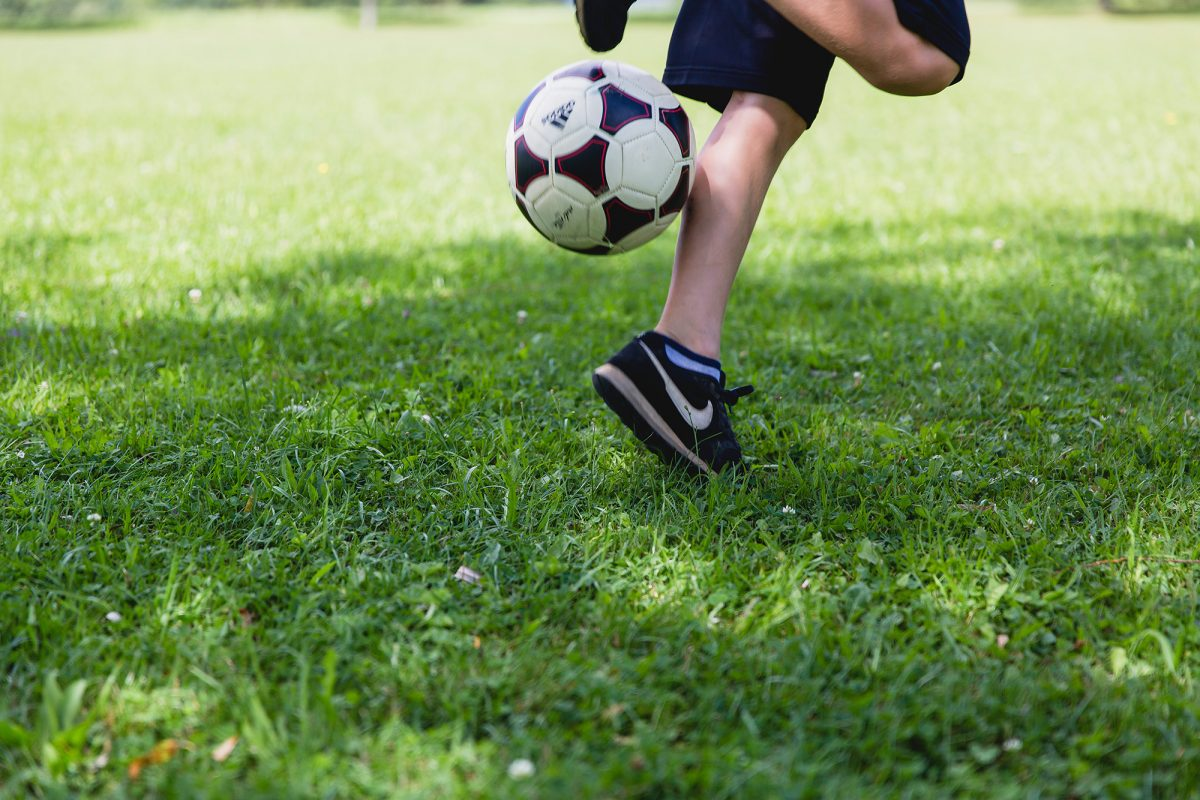Closeup of child's legs as they play with a football