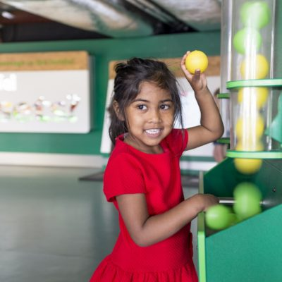 A girl in a red dress playing with tennis balls