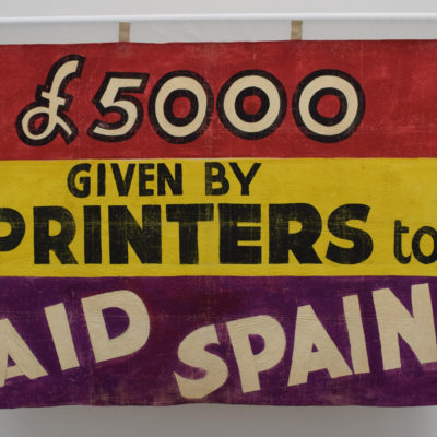 """A banner which says """"£5000 given by printers to aid Spain""""."""