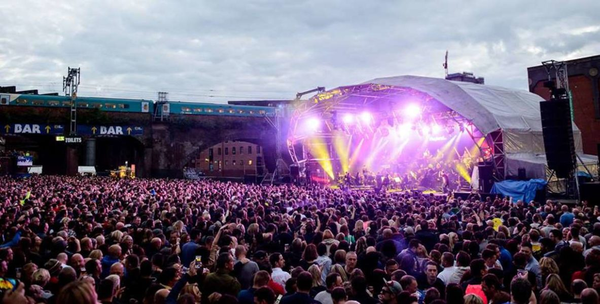 Crowds gather to enjoy themselves at a music concert in Castlefield Bowl.
