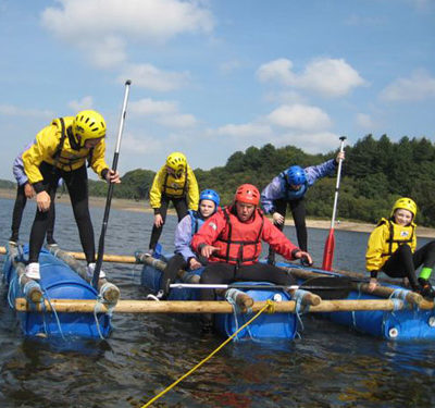 A group of young people sailing on a raft.