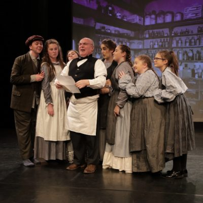 The MaD Theatre Company performing one of their plays in period costume on stage.