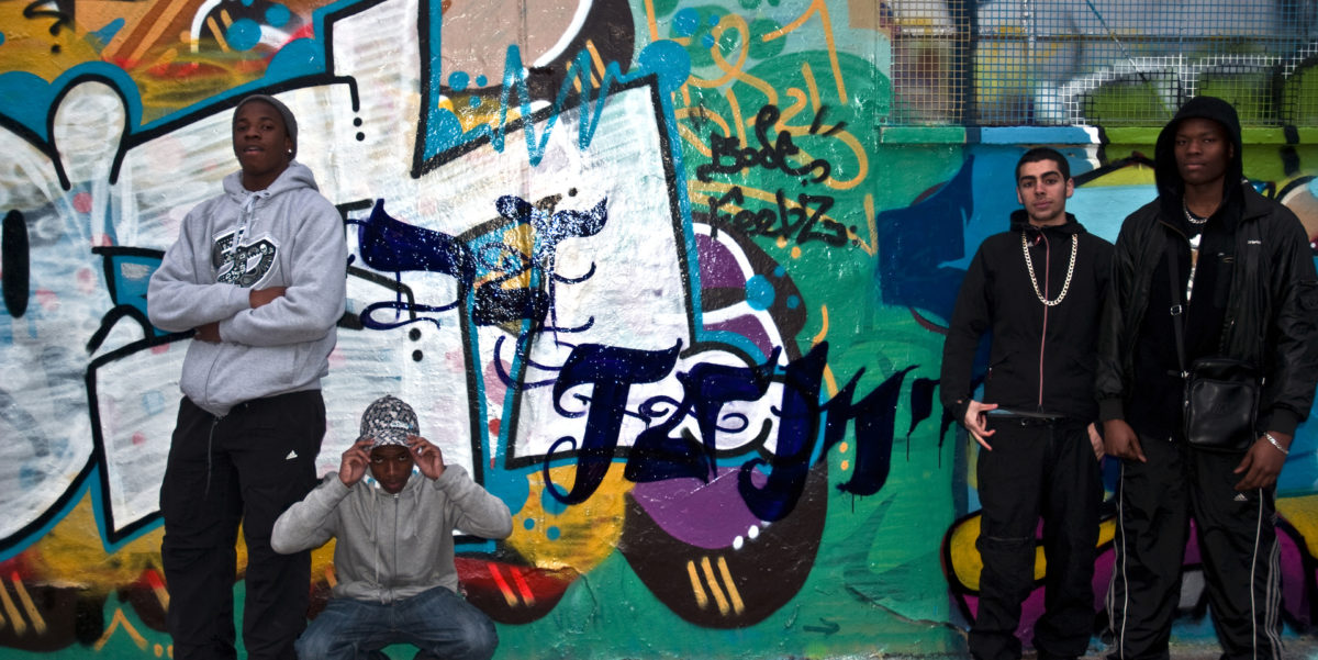 Members of the M13 Youth Project stand in front of a wall painted with some street art.