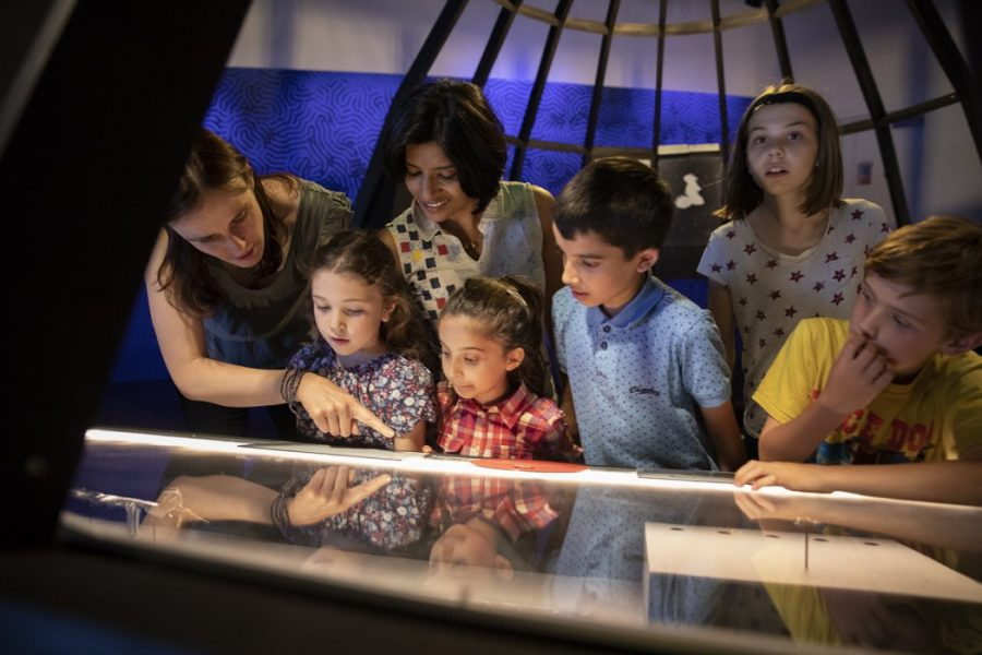 A family with young children look fascinated by an exhibition.