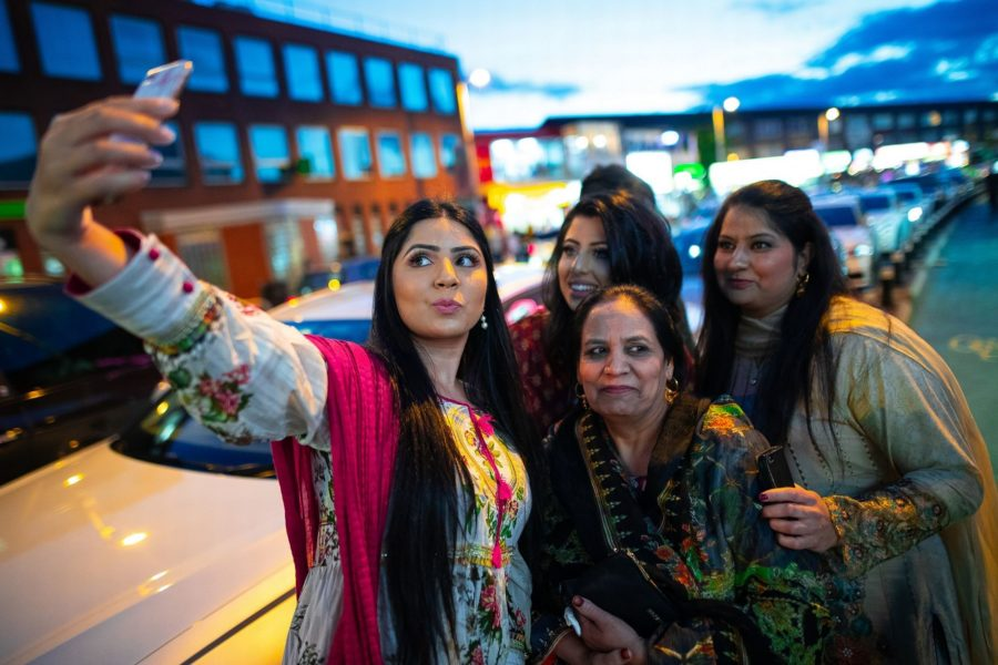A group of four women taking a selfie on the Curry Mile in Rusholme.