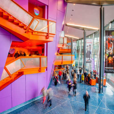 People walking around inside The Lowry in the daytime.