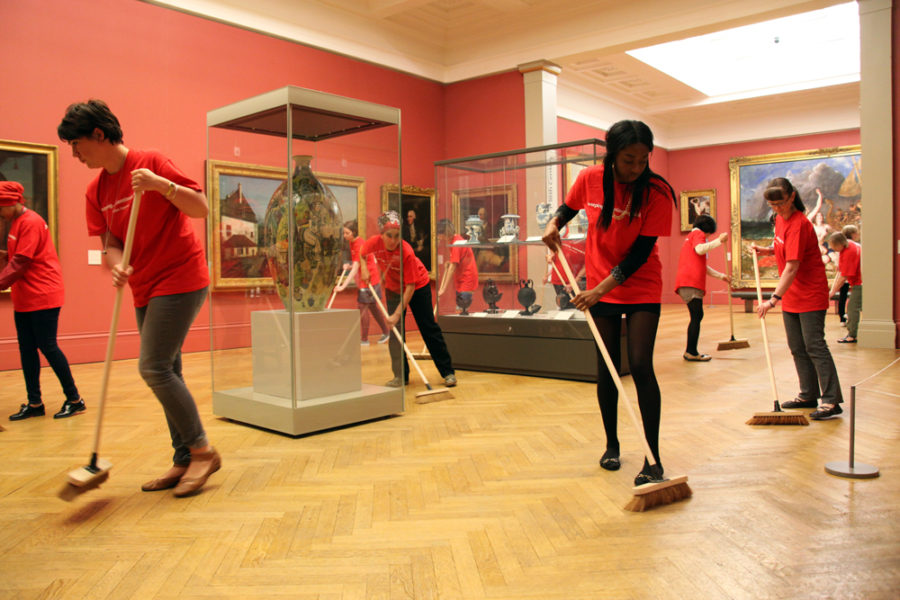 A group of cleaners sweep up inside Manchester Art Gallery.