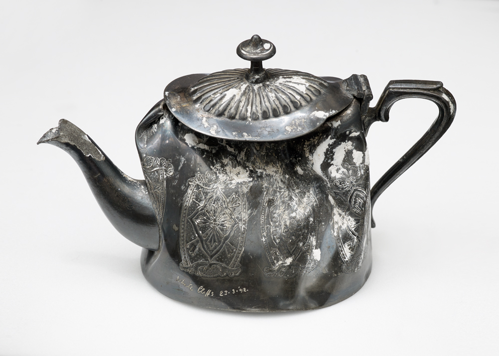An well-used, dented and tarnished tea pot.