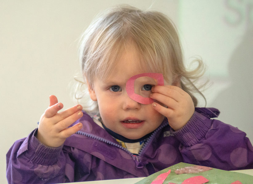 A toddler wearing a purple jacket peeks through a pink paper hoop she holds over her eye.