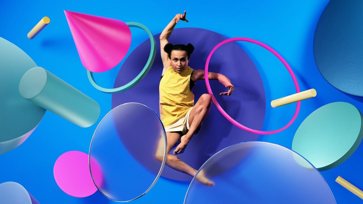 A dancer leaps through the air surrounded by colourful shapes.