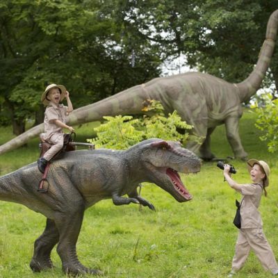 Two children dressed as explorers enjoy playing with a large model dinosaur.
