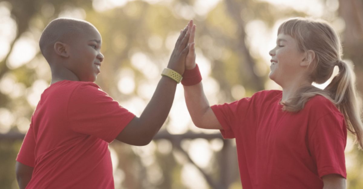 A boy and girl, both wearing red t-shirts, high-five eachother.