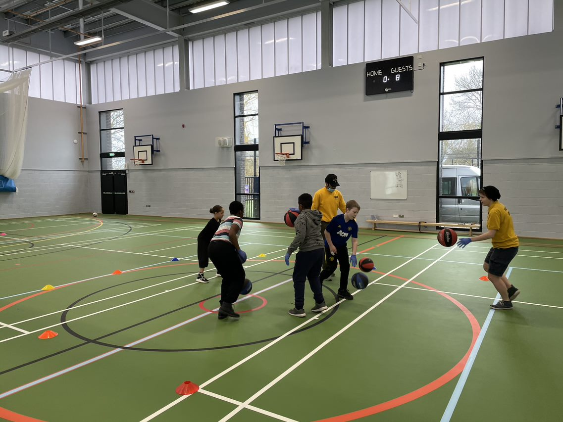 A group of young people play basketball in a sports hall.
