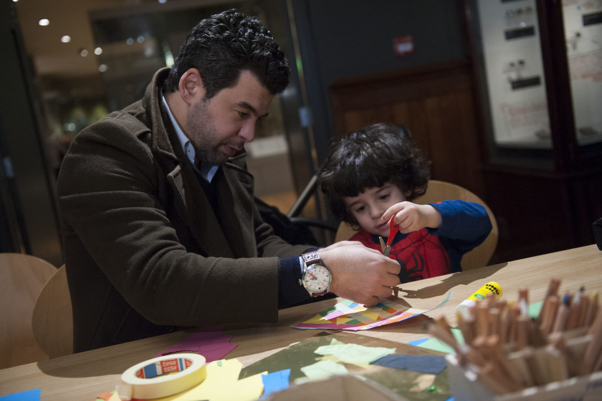 A Child and an adult enjoying a craft activity in the Manchester Museum.
