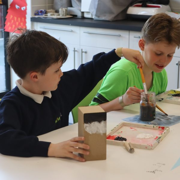 Two children enjoy an arts and crafts activity together.