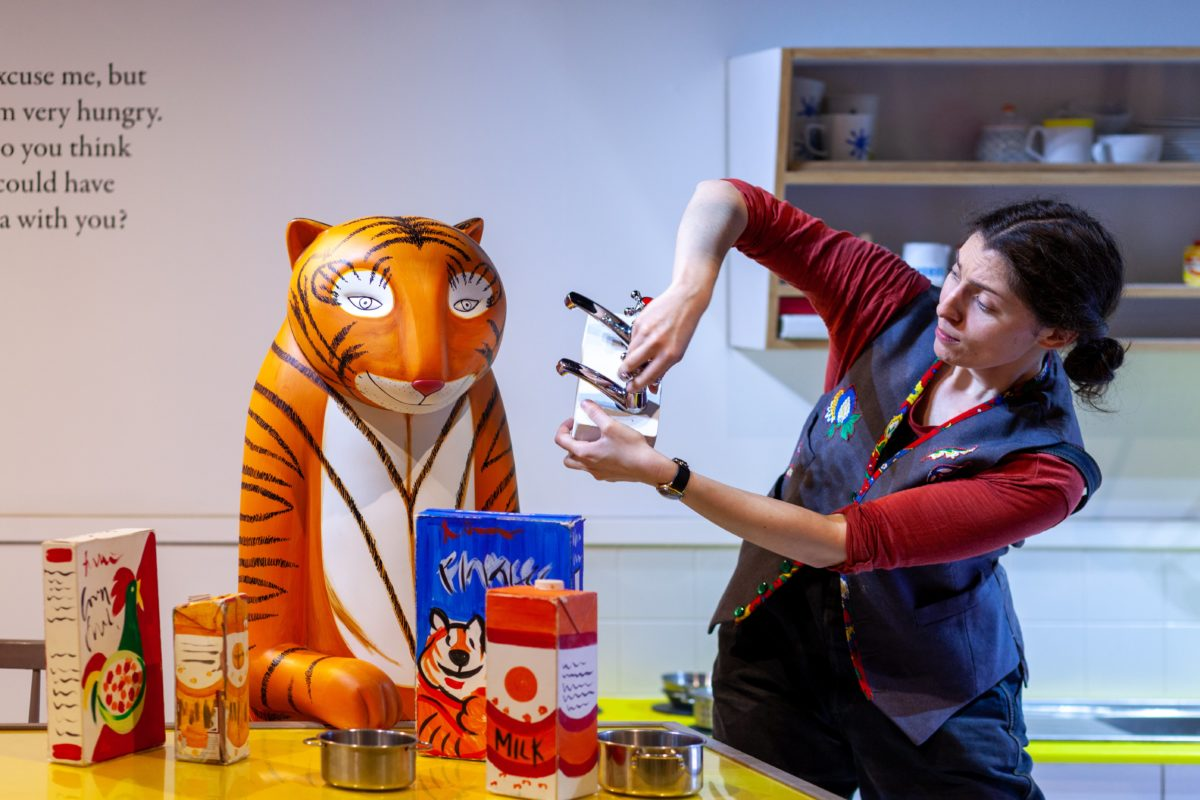A performer acts out the story from The Tiger Who Came to Tea with a model of the tiger and various props.