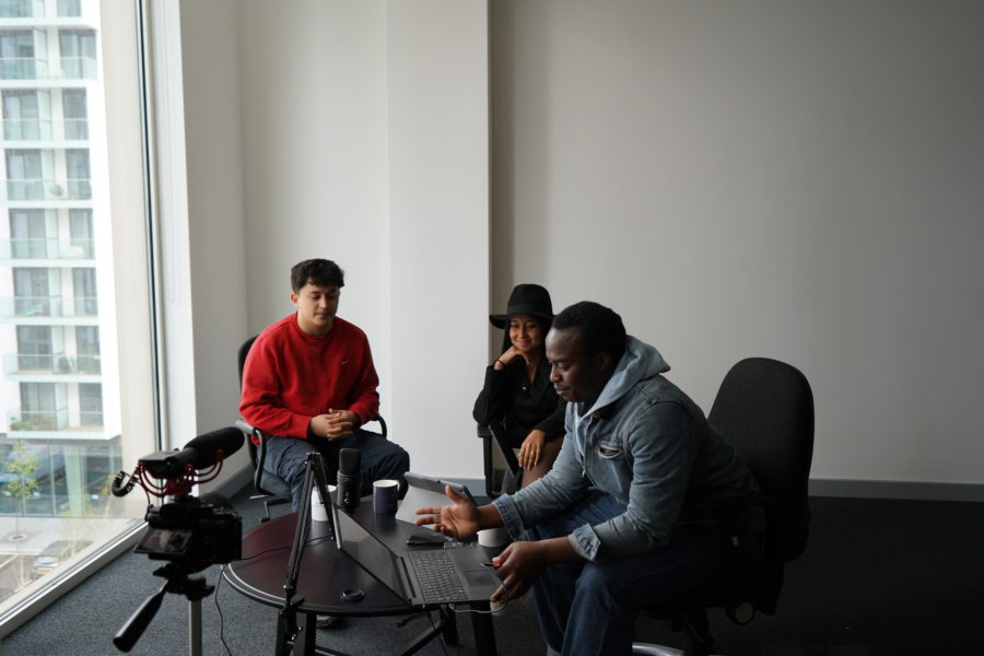 Three young people sit around a laptop for a discussion at the Black Youth Forum.