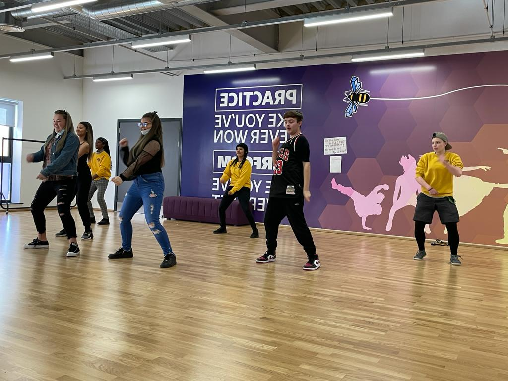 A group of young people enjoy a dance session in a fitness studio.