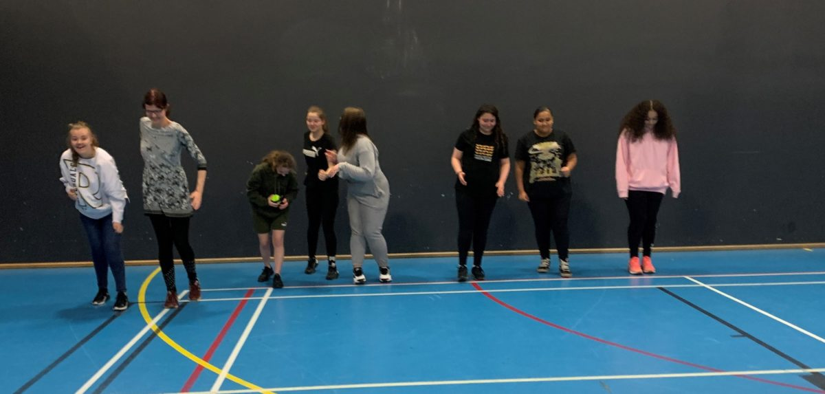 A group of young people ready to participate in a sports session in a sports hall.