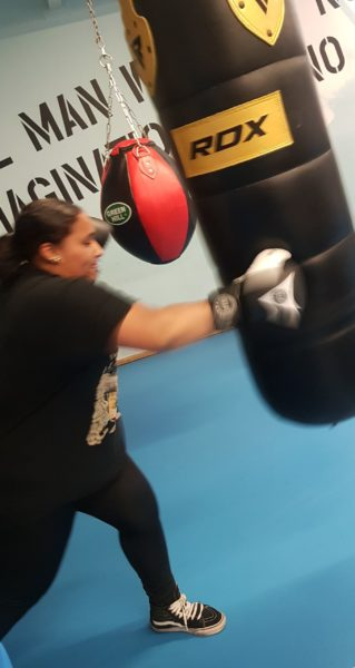 A young person wearin boxing gloves pounds a punching bag.