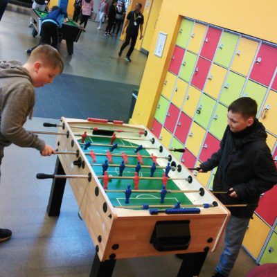 Two young people play table football at Manchester Youth Zone.