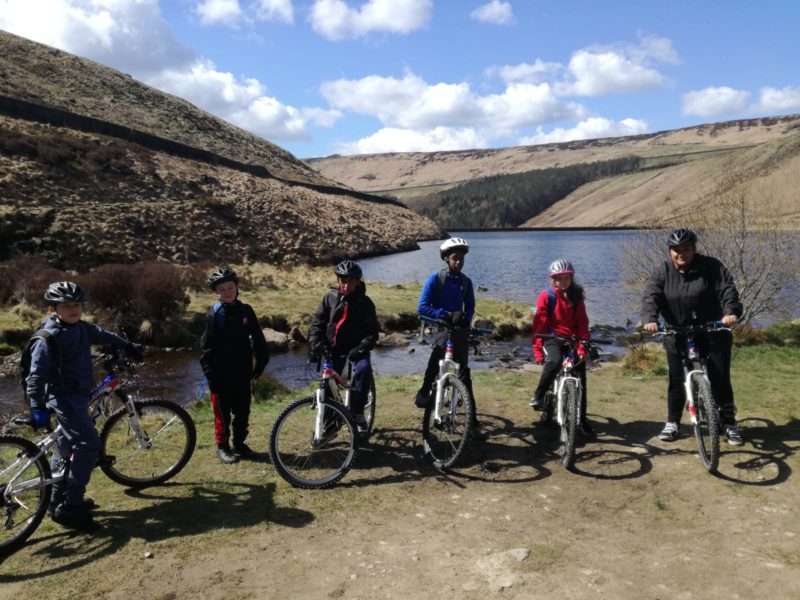 A group of young people get ready to set off on a mountain bike ride.
