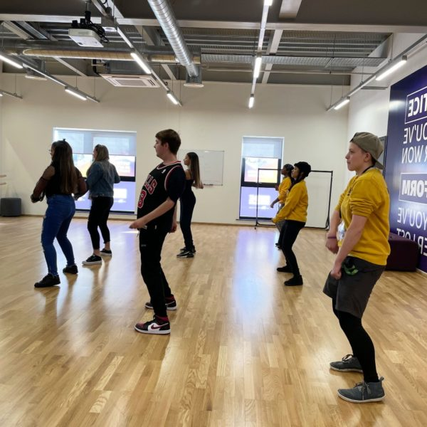 A group of young people enjoy a dance session in a studio.
