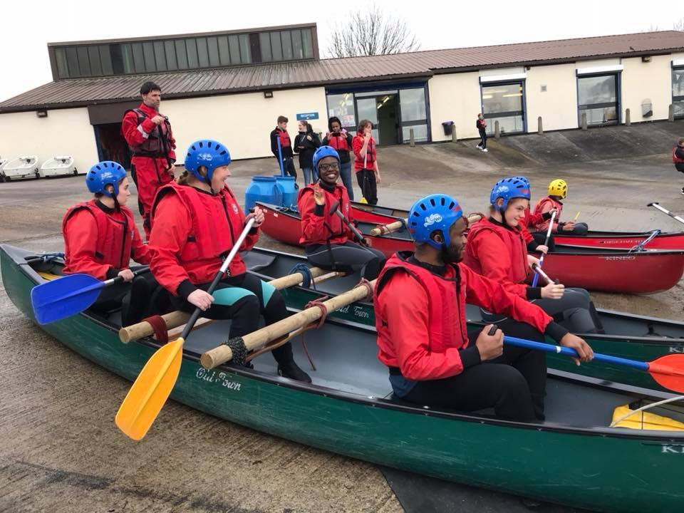 A group of young people sit inside canoes on the jetty at Debdale Outdoor Centre as they learn about sailing.