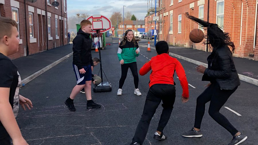 Youngsters playing sports together on Bakewell Street in Gorton, Manchester.