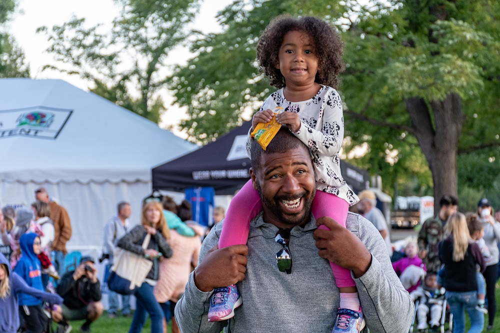 A small child sits on the shoulders of an adult at a festival.