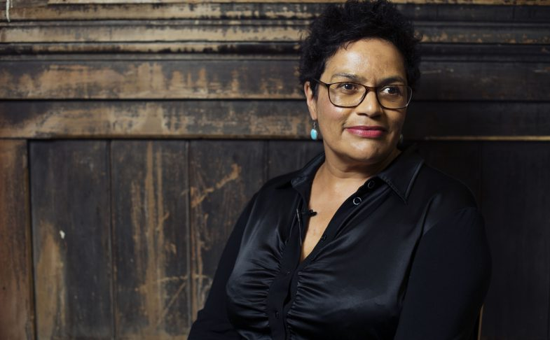 Poet Jackie Kay stands in front of a wooden panel.