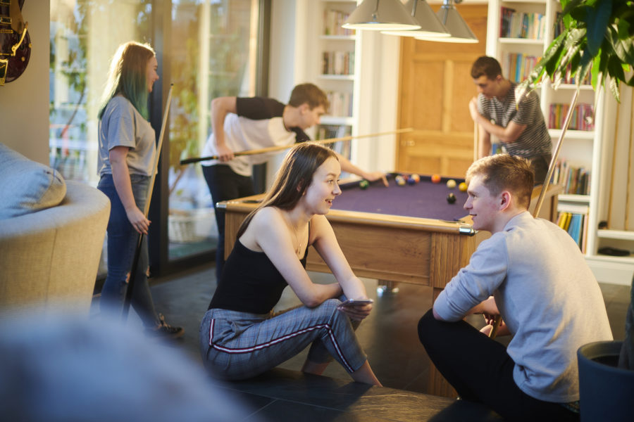 A group of teenage friends playing pool.