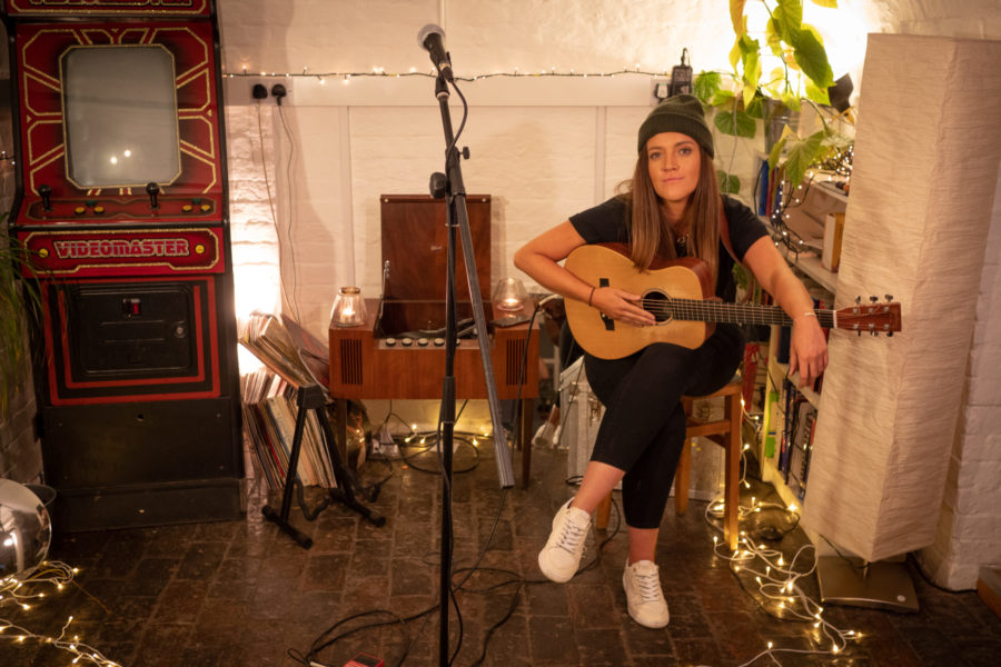 Performer and musician Lauryn Redding sits with a guitar close to her microphone.