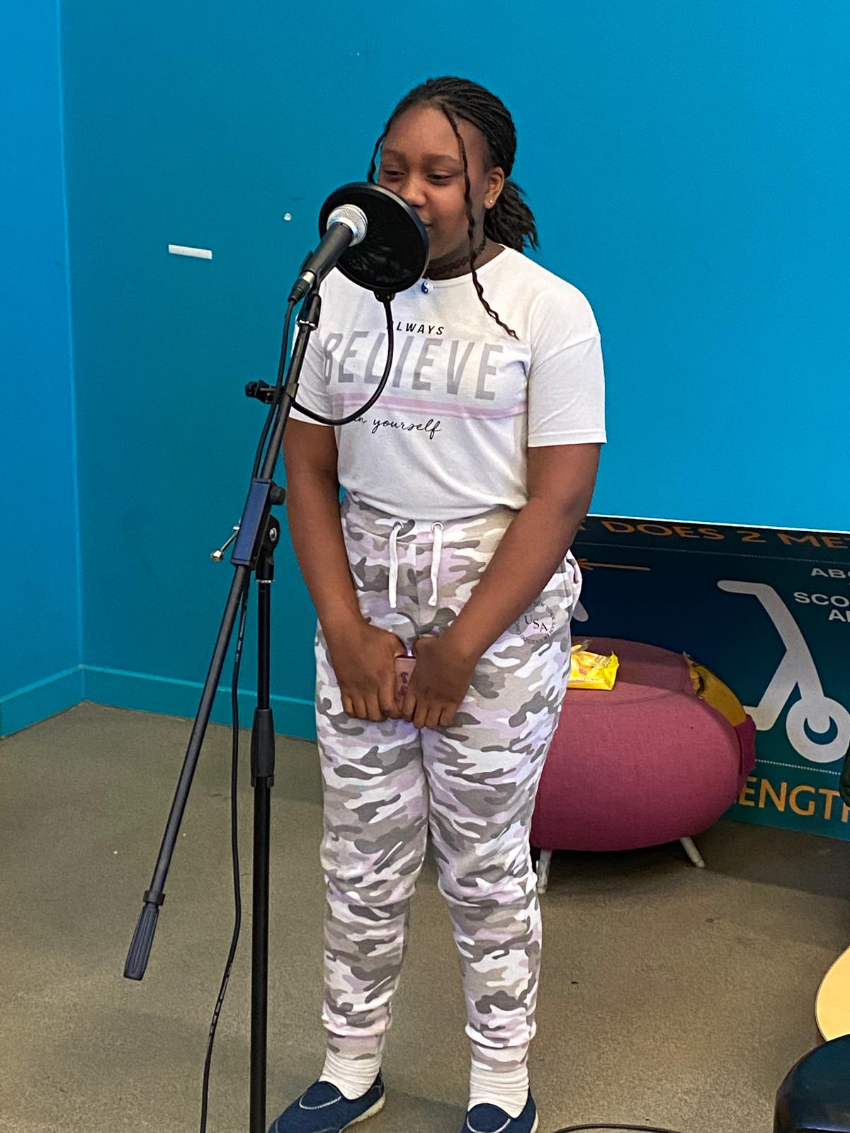 A young person sings into a microphone at a drama workshop.