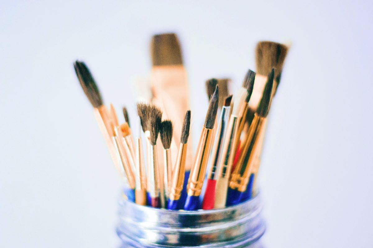 A pot filled with paint brushes