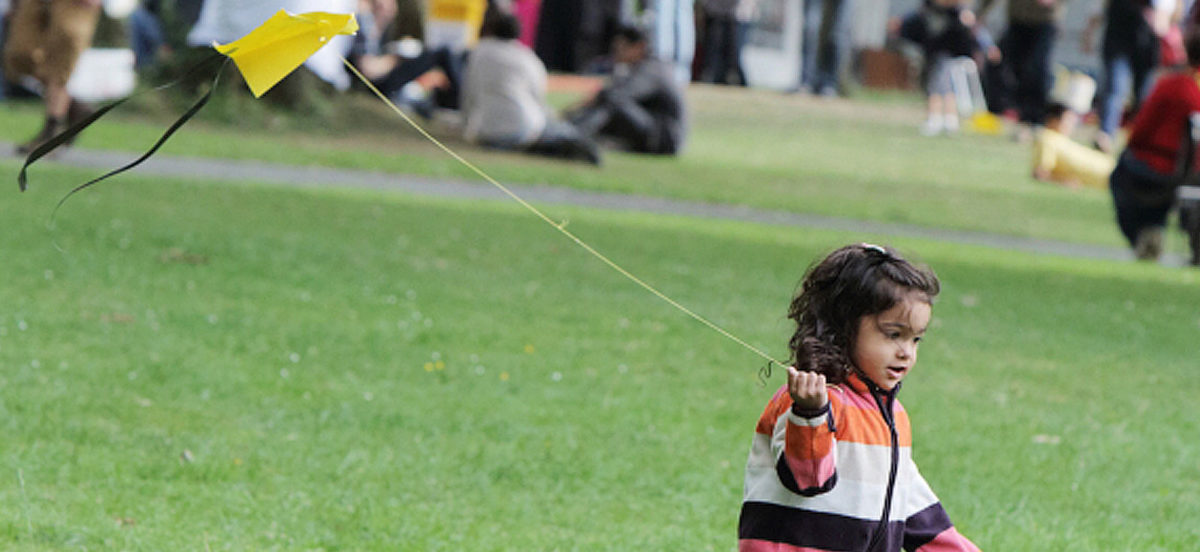A young child walks across a grass field with a kite.